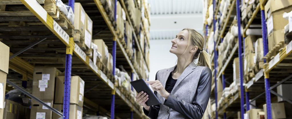 Background image - industry solution procurement & logistics - view women with a tablet in a warehouse