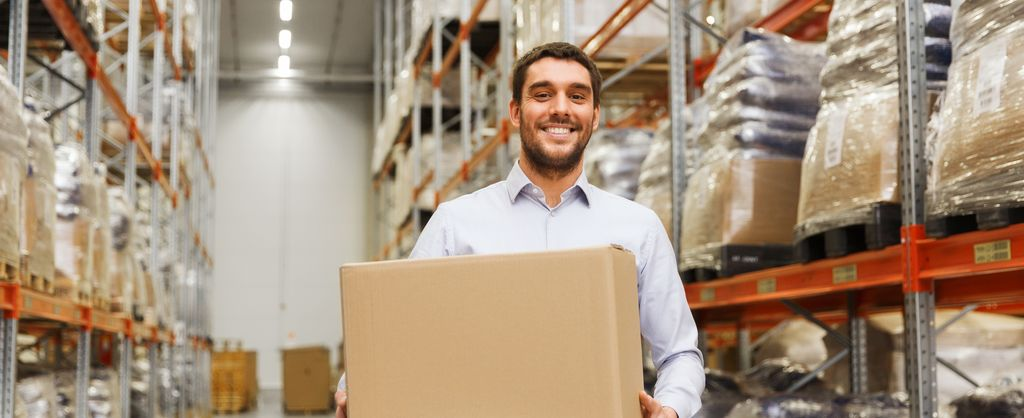Background image - industry solution wholesale & retail trade - view of a smiling men in a warehouse